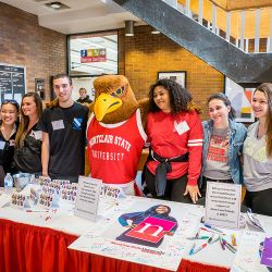 Montclair State University students posing for a photo with Rocky the Red Hawk at Red Hawk Day of Thanks.