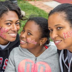Female Montclair State University student with sister and mother at homecoming.