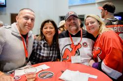 alumni at NJ Devils game in team jerseys