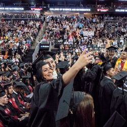 A pair of female Montclair State University students taking a selfie at Commencement.