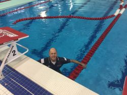 Photo of swim coach McLaughlin in the pool, fully dressed.