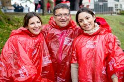 Alumni with parents wearing rain ponchos at Homecoming 2018