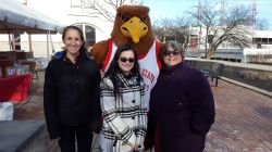 Three people standing with Rocky the Red Hawk