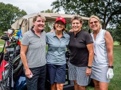 Group of alumnae smiling at Red Hawk Open