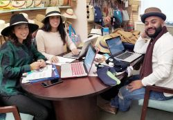 Three students wearing hats sitting at table discussing fashion merchandising