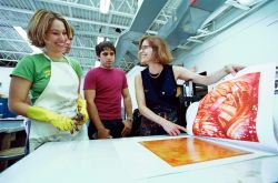 Instructor discussing printmaking with two students