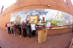 people standing in front of mural