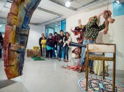 "Attendees at the MFA Open Studio 2013 event look on at the creative process of MFA student, Teresa Braun, and her ""Slaughter Fest."""