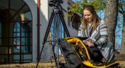 Journalism student Catherine Baxter sets up for a shoot with a mobile media backpack.