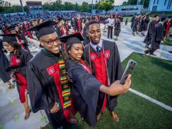 three students posing for selfie at convocation