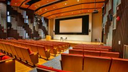 Presentation Hall with large stage and screen and seating at the School of Communication and Media