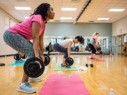Two people in a group fitness class lifting weights