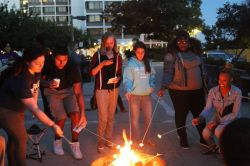 Group of students roasting marshmallows on a fire