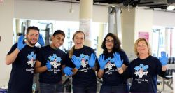 The staff of Campus Recreation posing for a picture wearing blue gloves.