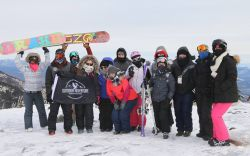 Group of skiers and snowboarders on top of a mountain