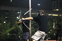 Two male students playing archery tag at night