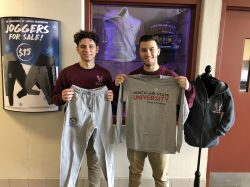 Two students holding up grey long sleeve shirt and sweatpants