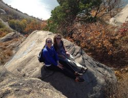 Two girls sitting on a rock at an overlook on a sunny day