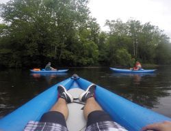 View from a the perspective of someone in a kayak, looking at two other kayaks on a river