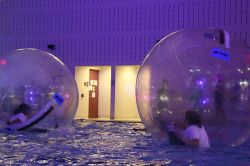 Two students participating in the Hamster Glow in the Student Recreation Center Pool.