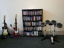 A book shelf that has an assortment of DVDs on it. On the left of the book shelf are two rock band guitars, and on the right is a rock band drum set.