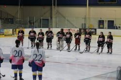 Nine people in a black hockey uniform, on an ice hockey field facing another line of hockey members