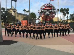 A group of females from the dance team standing in V formation in front of a globe statue that reads ESPN wide world of sports complex.