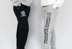 two students wearing black and gray joggers. the black joggers have a small campus recreation logo and underneath say montclair state university campus recreation. and the gray joggers have a small campus recreation logo and say montclair state university campus recreation going down the leg
