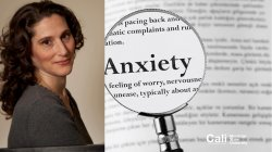 "Woman with magnifying glass over word ""Anxiety"""