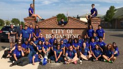 Group of Center for Community Engagement students in front of the City of Brigatine Brick Sign