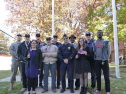 Students and Veterans posing for a photo at a flag raising.