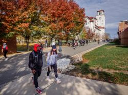 Two students on a fall day walking on campus