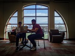 two students studying inside near a window