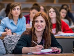 photo of female student smiling and taking notes in class