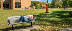 Student in outside of Dickson hall lying on bench