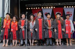 graduates on stage in commencement regalia