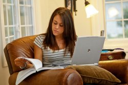 student studying at home with laptop and notebook