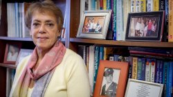 Photo of Professor Deborah Ragin in front of bookshelf with books and picture frames