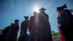 photo of students in black cal and gown with sunlight behind them