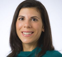 headshot of professor Laura Lakusta in green top and white background