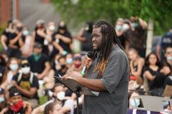 Jason Williams holding a microphone and speaking at an outdoor demonstration. a crowd is blurred in the background