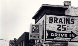 black and white image of old building with large advertisement painted on side. Sign reads Brains 25 cents