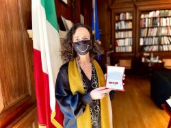 photo of Teresa Fiore with black face mask with white smile. Italian flag is in the background in an office with bookshelves