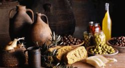 stock image of mediterranean table with breads, cheese, olives and oils