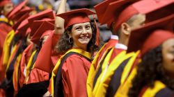 Female Montclair State University graduate clad in cap and gown smiling.