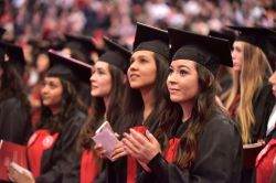Photo of two female Montclair University undergraduates clad in graduation gowns looking up.