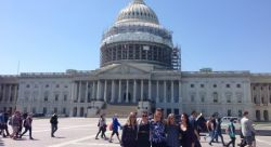 Picture of Capitol Hill with Students posing in front.