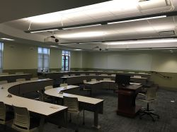 Another example of a breakout room/lecture hall. Some chairs with rounded tabletops surround a single lectern.