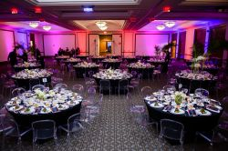 The Main Ballroom of the Conference Center set up with multi-colored lighting and tables and chairs.