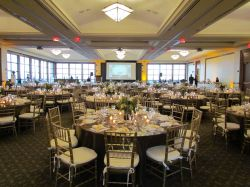 The Main Ballroom set up with gold and white chairs and a dining setup.